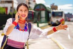 Vrij jonge vrouw die traditionele Andesblouse en blauwe rugzak dragen, die op bus bij in openlucht postplatform wachten Stock Afbeelding
