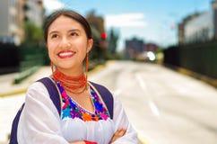 Vrij jonge vrouw die traditionele Andesblouse en blauwe rugzak dragen, die op bus bij in openlucht postplatform wachten Stock Foto's