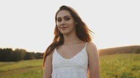 Vrij jonge vrouw in een goede stemming die zich op gebied op de zomeravond bevinden Lang haar die in wind stromen stock videobeelden