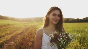 Vrij jonge vrouw in een weide met boeket van wilde bloemen op de zomeravond Haar die in wind stromen stock footage