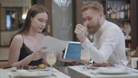 Vrij jonge vrouw en blonde gebaarde man zitting bij de lijst in de koffie die informatie over het laptop scherm bespreken stock footage