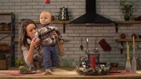 Vrij jonge vrouw en leuke baby in haar wapens die zich in moderne keuken bevinden Gelukkig familieconcept stock footage