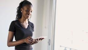 Vrij jonge vrouw gebruikend haar digitale tablet en thuis bekijkend camera naast het venster stock video