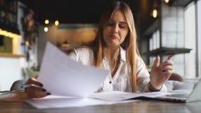 Vrij jonge vrouw gebruikend laptop en luisterend aan muziek met hoofdtelefoons op het werk stock videobeelden