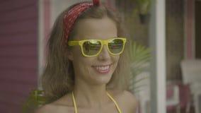 Vrij jonge vrouw gele bikini dragen en zonnebril glimlachen die geïsoleerd op de achtergrond van roze huis stock footage