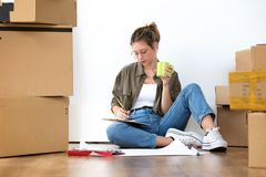 Vrij jonge vrouw het schrijven inventaris van haar bezittingen van haar nieuw huis terwijl thuis het zitten op de vloer royalty-vrije stock afbeelding