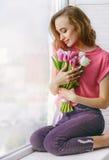 Vrij jonge vrouw met boeket van tulpen op vensterbank Stock Foto