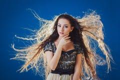 Vrij jonge vrouw met lang haar op blauwe achtergrond Stock Afbeeldingen