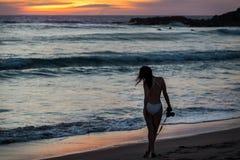 Vrij jonge vrouw op een strand bij zonsondergang met een camera in haar hand royalty-vrije stock foto