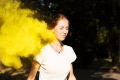 Vrij jonge vrouw in trillende kleuren die rond haar bij HOL exploderen Stock Fotografie
