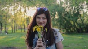 Vrij jonge vrouwen glimlachende en ruikende bloemen in het park stock footage