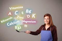 Jonge vrouwen kokende vitaminen en mineralen Stock Afbeeldingen