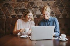 Vrij jonge vrouwen met laptop door de lijst Royalty-vrije Stock Foto
