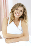 Vrij jonge vrouwenzitting op het bed met hoofdkussen Stock Afbeeldingen