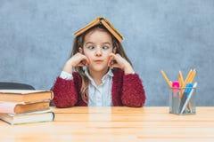 Vrij krullende meisjeszitting en holding een boek over haar hoofd over een grijze achtergrond Tijdens dit schoolmeisje neemt haar stock foto's