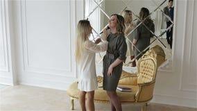 Vrij maakt de jongelui omhoog kunstenaar werkt met model dichtbij de grote spiegel en de gouden bank stock videobeelden