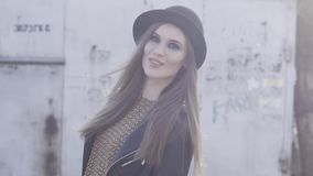 Vrij in meisje met het zwarte modieuze hoed en leerjasje stellen bij de oude bouw in warm zonlicht actie Het glimlachen stock videobeelden