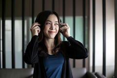 Vrij mooie Aziatische vrouw die hoofdtelefoon en het luisteren muziek dragen stock afbeelding