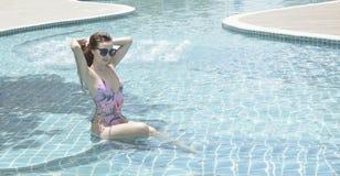 Vrij mooie vrouw die in roze bikini met zonnebril zitten royalty-vrije stock afbeeldingen