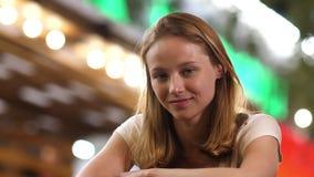 Vrij nadenkende jonge vrouw die met blond haar glimlachend aan camera kijken stock videobeelden