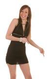 Vrij neer brunettepointing aan haar linkerzijde Stock Afbeelding