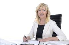 Vrij rijpe bedrijfsvrouw die op bureau glimlachen Stock Afbeeldingen