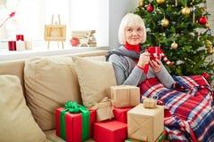 Vrij rijpe vrouw door Kerstboom stock foto's