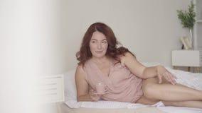 Vrij rijpe vrouw het drinken thee of koffie die in bed in de ochtend liggen Glimlachende dame die thuis ontspannen De zon glanst  stock videobeelden