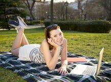 Vrij rode haarvrouw die aan laptop in park werken Royalty-vrije Stock Afbeelding