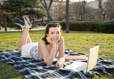 Vrij rode haarvrouw die aan laptop in park werken Royalty-vrije Stock Foto's