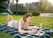 Vrij rode haarvrouw die aan laptop in park werken Stock Afbeeldingen