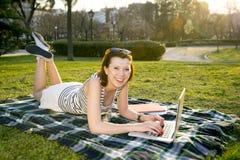 Vrij rode haarvrouw die aan laptop in park werken Royalty-vrije Stock Afbeeldingen