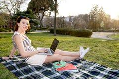 Vrij rode haarvrouw die aan laptop in park werken Stock Foto's