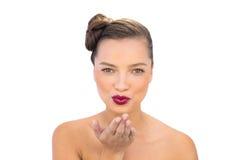 Vrij schitterende vrouw met rode lippen die luchtkus blazen Stock Afbeelding