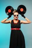 Vrij speld-op vrouw met het retro kapsel en samenstellings stellen met vinylverslag over blauwe achtergrond royalty-vrije stock foto's