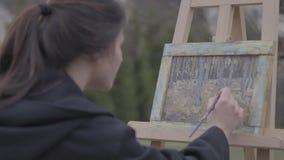 Vrij succesvolle kunstenaarsverven op het canvas in de binnenplaats Mooi enthousiast meisje belast met creativiteit Art stock footage