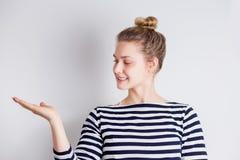 Vrij vrolijke vrouw met schone huid, natuurlijke make-up die palm op exemplaarruimte tonen, die uw product voorstellen stock foto