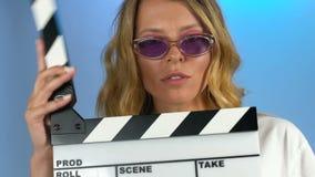 Vrij vrouwelijk camera hulp gevend signaal met clapperboard, film het schieten stock videobeelden