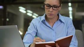 Vrij vrouwelijk werknemer het schrijven werkplan in notitieboekje, om lijst, creatieve ideeën te doen stock footage