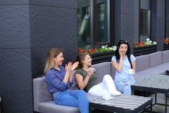 Vrij vrouwelijke bij koffie lachen en vrienden die, het drinken koffie roddelen Stock Afbeelding
