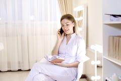 Vrij vrouwelijke cosmetologist die door smartphone bij kabinet spreken Royalty-vrije Stock Fotografie