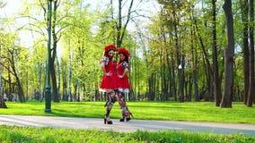 Vrij vrouwelijke dansers in folklore gestileerde kostuums en bloemcirclets in park stock videobeelden