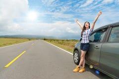 Vrij vrouwelijke toerist die zich naast reisauto bevinden stock foto