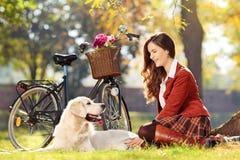 Vrij vrouwelijke zitting neer met haar hond in park Stock Afbeeldingen