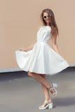 Vrij zoet mooi meisje in een heldere witte kleding in modieuze schoenen en zonnebril die op het dak spinnen Stock Foto's