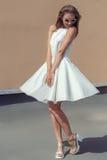 Vrij zoet mooi meisje in een heldere witte kleding in modieuze schoenen en zonnebril die op het dak spinnen Stock Fotografie