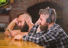 Vrijdagontspanning in bar Besteedt de Hipster gebaarde mens vrije tijd bij barteller Ordedranken bij barteller Mensen met stock afbeeldingen