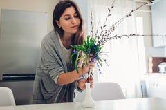 Vrije allergie Gelukkige vrouw die de lentebloemen in vaas op keuken zetten Seizoengebonden allergieconcept stock foto's