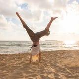 Vrije Gelukkige Vrouw die Cartwheel draaien die van Zonsondergang genieten op Sandy Beach stock afbeelding