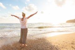 Vrije Gelukkige Vrouw die van Zonsondergang op Sandy Beach genieten Royalty-vrije Stock Afbeeldingen